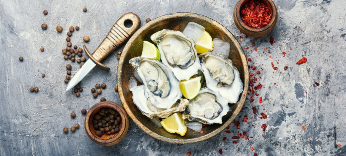 Fresh oysters on cutting board of ice and lemon